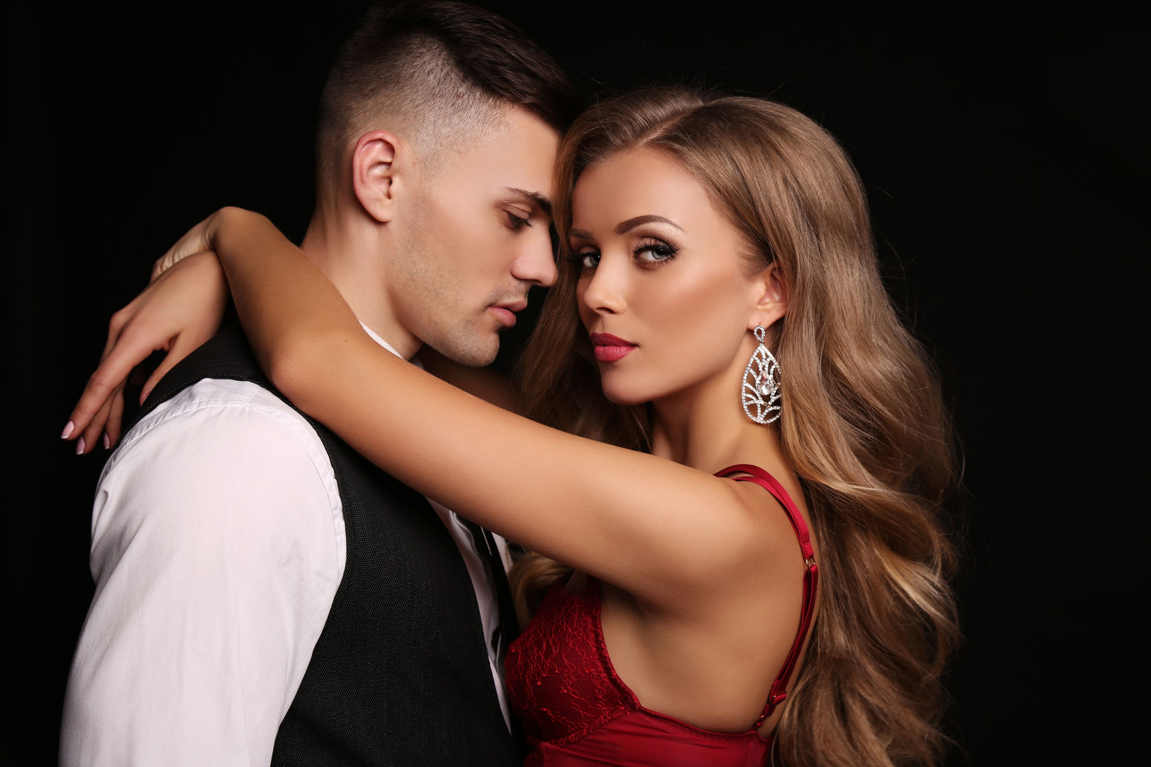 51693375 - fashion studio photo of beautiful couple in elegant clothes, gorgeous woman with long blond hair embracing handsome brunette man