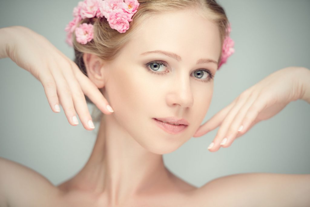 30695158 - beauty face of the young beautiful woman with pink flowers in her hair